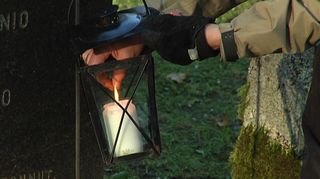 Kynttilää sytytetään hautausmaalla.