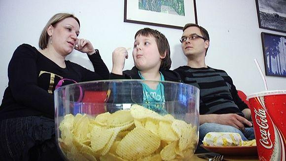 Nainen, lapsi ja mies istuvat sohvalla.