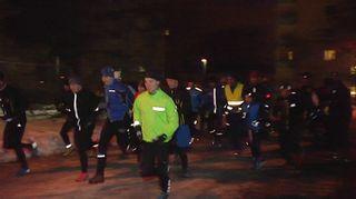 Suuri joukko ihmisiä juoksemassa pimeässä