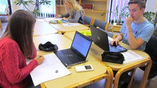 Lukiolaiset työskentelevät pöydän ääressä