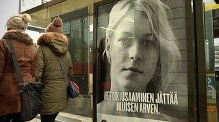 Ihmiset kävelevät nettikiusaamisesta kertovan mainoksen ohi.