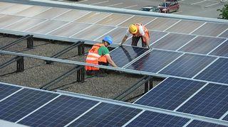 Miehet asentavat aurinkopaneeleja talon katolle.