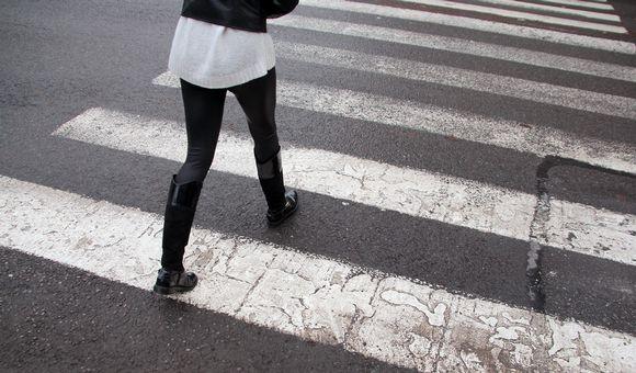 Henkilö kävelee suojatiellä