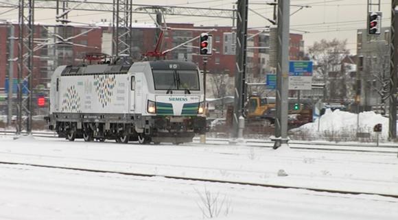 Hybridiveturi Vectron kulkee lumisessa kaupunkimaisemassa Turun ratapihalla.