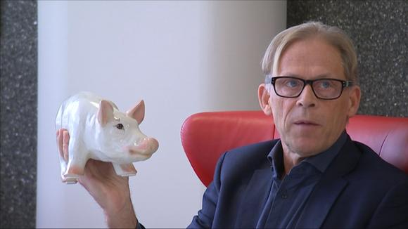 Liikemies Toivo Sukari pitää sikapatsasta kädessään