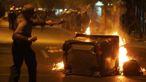 Mielenosoittaja heittelee kiviä mellakkapoliiseja kohden.