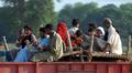 Pakistanin tulvan uhreja matkaa kuormineen kuorma-auton lavalla.