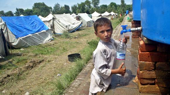 Pikkupoika hakee vettä vesisäiliöstä pakolaisleirillä.