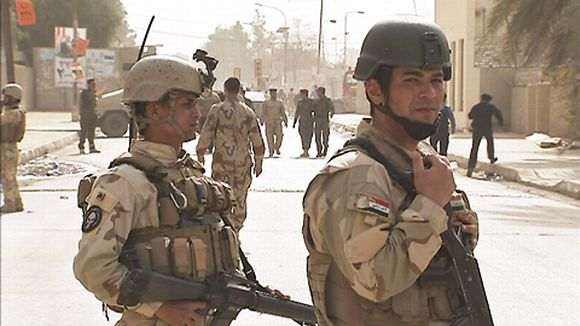 Kaksi sotilasta partioi kadulla.