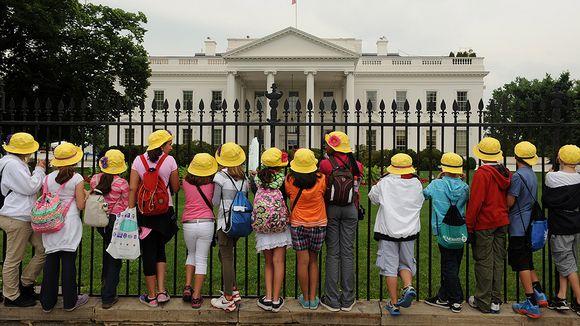 Lapset katselevat Valkoista taloa aidan takaa.