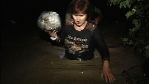 Nainen kahlaa vyötäröön asti yltävässä tulvavedessä pimeässä.