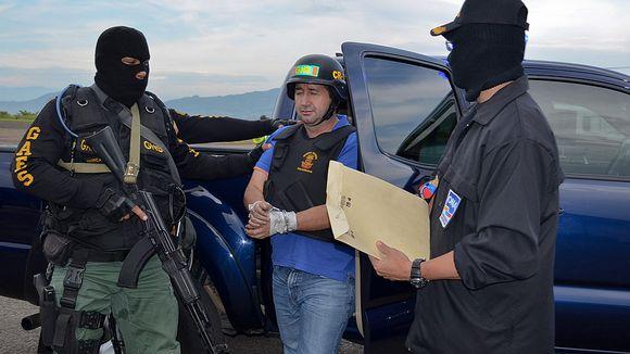 Venezuelan turvallisuusjoukkojen jäsenet saattavat huumeparoni Daniel Barreraa autosta.