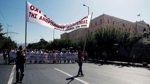 Lakkoilevat toimittajat marssivat kadulla Ateenassa.