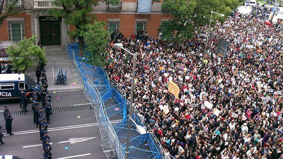 Mielenosoittajat kerääntyvät poliisin pystyttämän katusulun edustalle Neptuno-aukiolla.