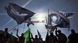 Mielenosoittajat heiluttavat lippuja.