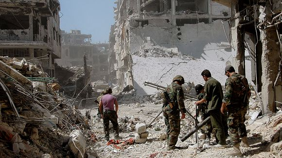 Syrian army soldiers patrol in a suburb of Homs.