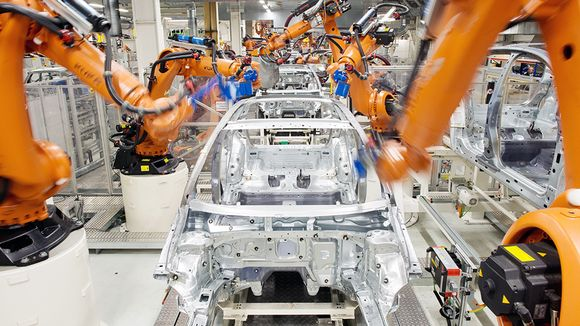 Robotit kasaavat autoja Volkswagenin tehtaan liukuhihnalla Saksan Wolfsburgissa.
