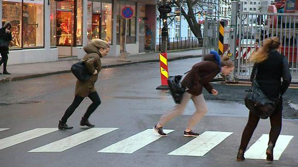 Video: Ihmiset ponnistelevat tuulta vastaan kadulla.