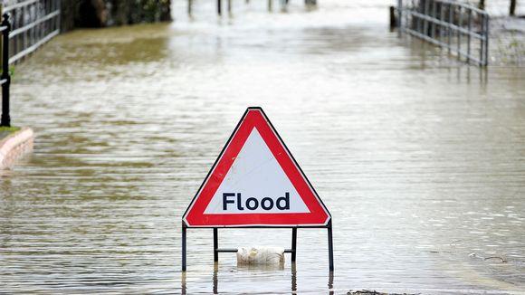 Flood-tulvakyltti veden valtaamalla kadulla.