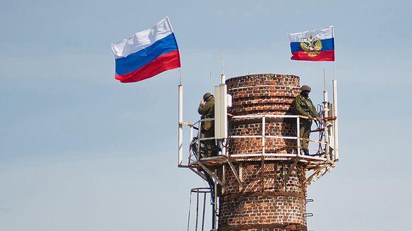 Kaksi venäläissotilasta ja Venäjän lippua suuren savupiipun päässä.