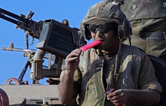 Israelilaissotilas söi jäätelöä Markava-panssarivaunun päällä matkalla Gazan-kaistaleelle 27. heinäkuuta.