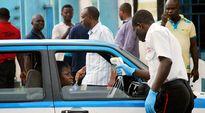 Hoitaja mittasi kuumetta auton kyydissä olevalta naiselta Port Harcourtissa, Nigeriassa tiistaina.