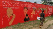 Nainen käveli ebolan tarttumisesta kertovan seinämaalauksen ohi Monroviassa, Liberiassa maanantaina.
