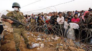 Turkkilaissotilas vartioi Syyrian vastaiselle rajalle kerääntyneitä pakolaisia lähellä Sanliurfan kaupunkia 27. syyskuuta.