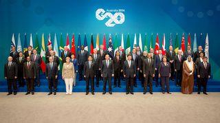 Kokouksen osanaottajat ryhmäkuvassa, maiden liput takana