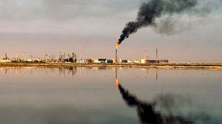 Öljynporaustorni syöksee tulta ja mustaa savua eteläisessä Irakissa, lähellä Umm Qasrin satamaa.