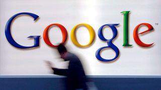 Mies kävelee ohi seinässä olevan Googlen logon.