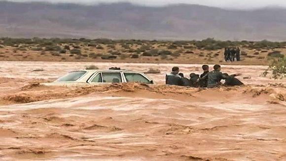 auto ja ihmisiä uponneina virtaavaan veteen