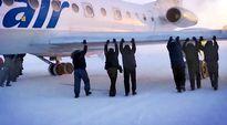 Matkustajat työntävät jäätynyttä lentokonetta Venäjän Siperiassa 52 asteen pakkasessa.