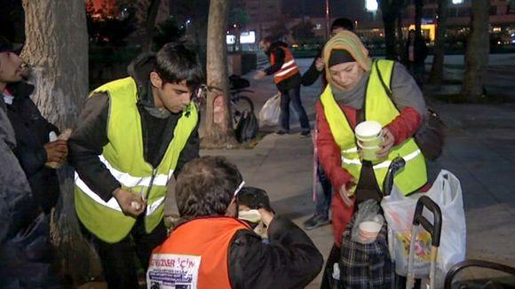 kaksi ihmistä jakaa yöllä keittoa kadulla asuville