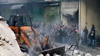 Ihmiset katselivat kun talojen raunioita jyrättiin Aleppossa viime helmikuussa.
