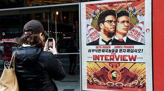 Nainen kuvaa elokuvajulistetta kännykkäkameralla kadulla.