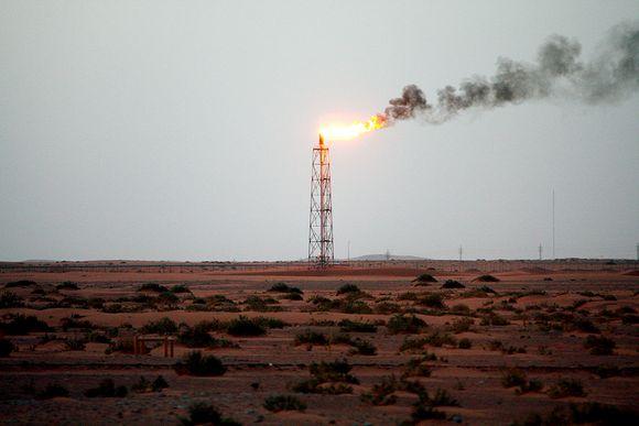 Yksinäinen kaasuliekki palaa aavikolla Khuraisin öljykentällä.