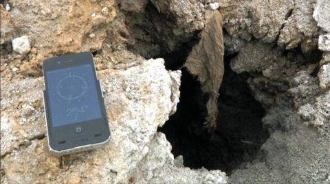 Älypuhelin räjähdyksen luoman kuopan vieressä.