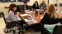 Argentiinan presidentti Cristina Fernández istuu pöydän päässä pyörätuolissa.