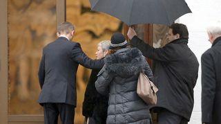 ovesta astuvan naisen yllä pidellään sateenvarjoa