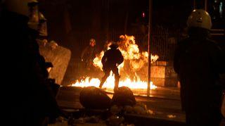 Mellakkapoliisit väistelivät polttopullon liekkejä hallituksen vastaisessa mielenosoituksessa Ateenan keskustassa 26. helmikuuta.