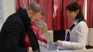 Virolaislapsi pudottaa äänestyslipukkeen uurnaan.