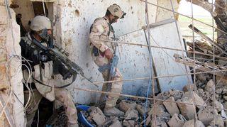 Irakilaissotilaat tarkastavat taistelun jälkiä.