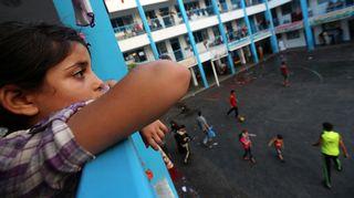 Kuvassa palestiinalaistyttö katsoo YK:n ylläpitämän koulun pihamaalle Gazassa. Kuva on otettu 3. elokuuta 2014.