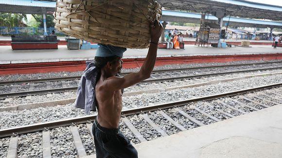 Mies kantaa koria päänsä päällä.