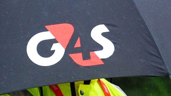 G4S-turvayrityksen logo työntekijän sateenvarjossa.
