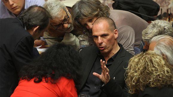 Kahdeksan ihmistä kuuntelee tarkkaavaisen näköisesti kun keskellä oleva Yanis Varoufakis puhuu heille.