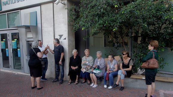 Ihmiset, joilla ei ole pankkikorttia, odottavat pankin ulkopuolella Ateenassa.