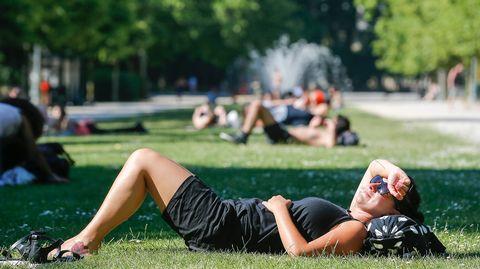 Auringonottajia puistossa Brysselissä, Belgiassa 1. heinäkuuta.