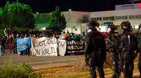 mielenosoittajia banderolleineen ja poliiseja
